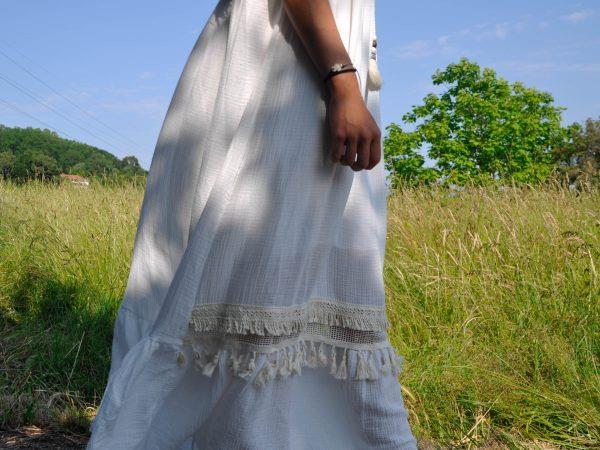 Vestido blanco estilo boho-chic con apliques de lentejuelas y flecos. Cordón trenzado en tonos beige rematado con pompón a tono.